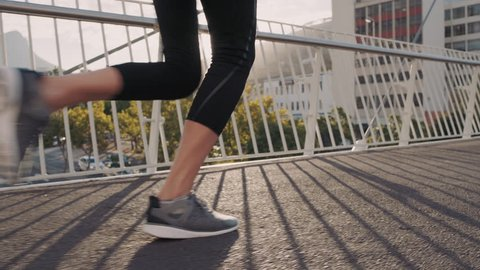 woman runner athlete legs jogging exercising running fitness lifestyle in early morning urban city slow motion