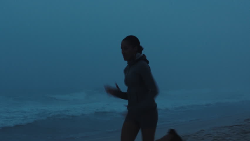 competitive women running on misty beach woman athlete overtaking in race competition challenge in stormy early morning seaside background #1012929686