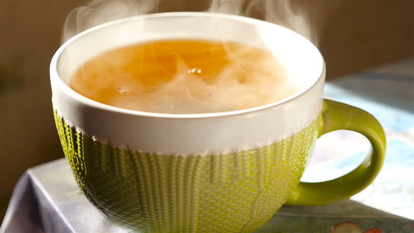 Tea in a large cup. Transparent steam. Slow motion