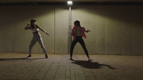 dancing woman young hip hop dancer girls under street light practicing contemporary freestyle dance moves practicing in city at night