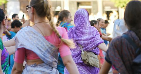 Kyiv, Ukraine - May 8, 2018: happy smiling women in Hindu traditional colorful costumes dancing and singing Hare Krishna mantra on the main street of Kiev in sunny summer day festival life celebration