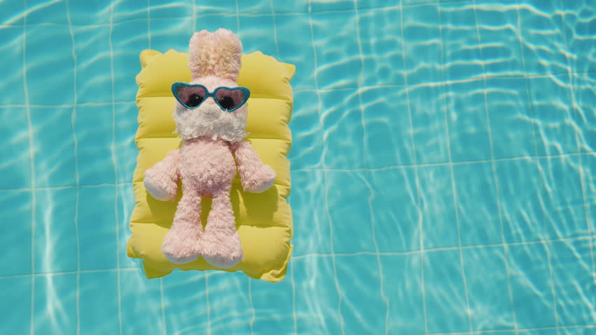 A cool rabbit in sun glasses glows on an inflatable mattress. Floats in the pool. Vacation with children
