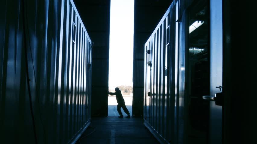 Worker Opening Warehouse Metal Door. Blue Steel Tone. Zoom Out.   Shutterstock HD Video #1012980476