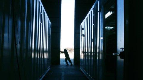 Worker Opening Warehouse Metal Door. Blue Steel Tone. Zoom Out.