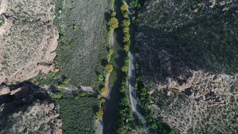 Aerial drone scene top view of Atuel river canyon in San Rafael, Mendoza, Cuyo Argentina. Camera moving forwards. Street next to the willows trees and river. Colorfull rocks.