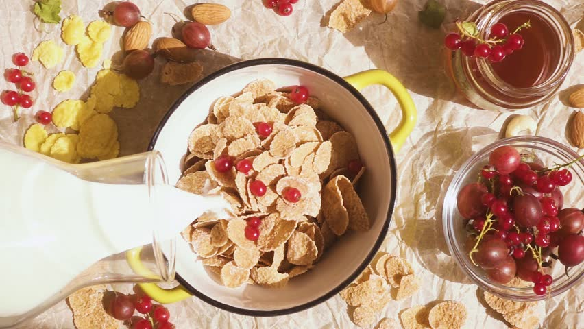 Milk from a glass bottle pour into a bowl with multi-cereal flakes and fruits slow motion | Shutterstock HD Video #1013006516