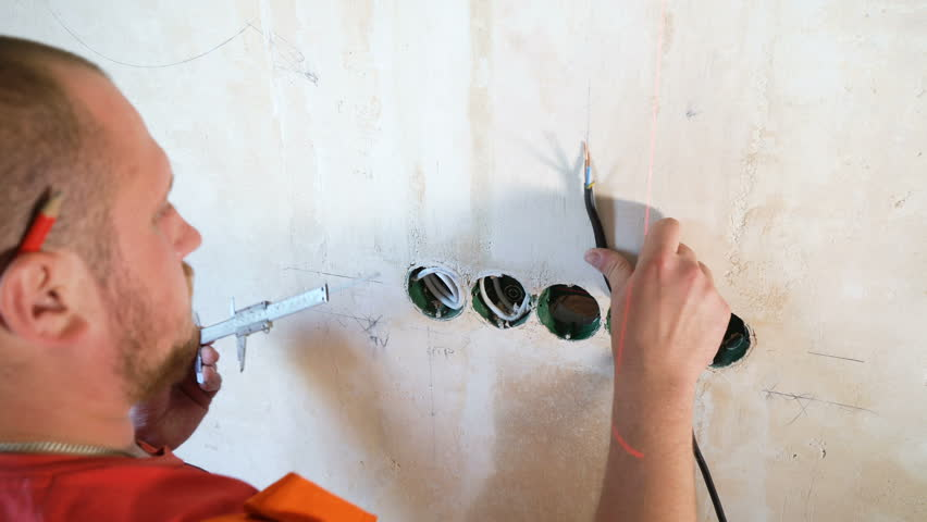 Closeup electrician checking technical parameters with calipers on building site. Worker control distance accuracy between installed wiring junction box on concrete wall. Safety policy, repair concept