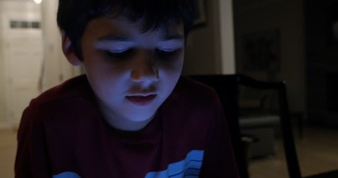 Young 10 year old boy's face illuminated by using a smart phone in his home