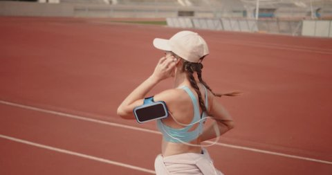 Young athletic woman doing sports practice by running on sports track and listening to music