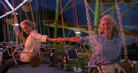 Mature women on summer holidays having fun sitting on swings during chairoplane ride at funfair