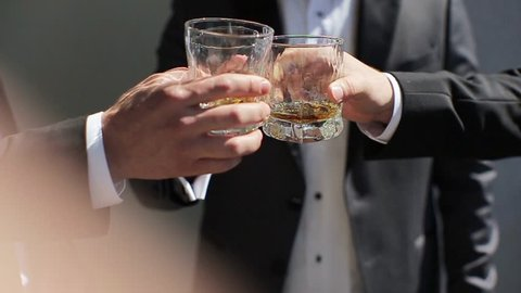 The groom and his friends drink whiskey