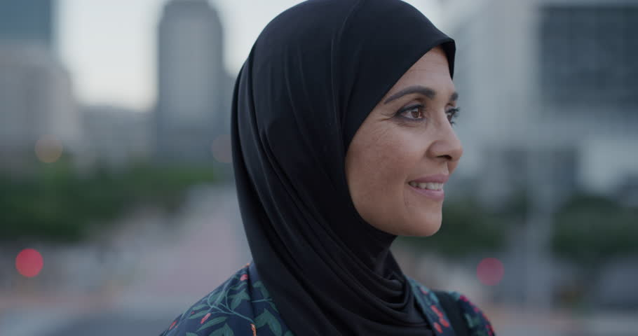 Slow motion portrait middle aged muslim woman turns head smiling confident enjoying successful urban lifestyle independent senior female wearing hijab headscarf in city at sunset | Shutterstock HD Video #1013050976