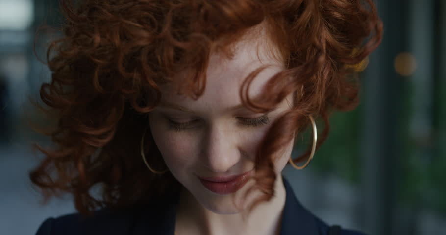 Close up portrait young beautiful business woman smiling looking at camera wind blowing hair cute red head female feminine beauty slow motion real people series