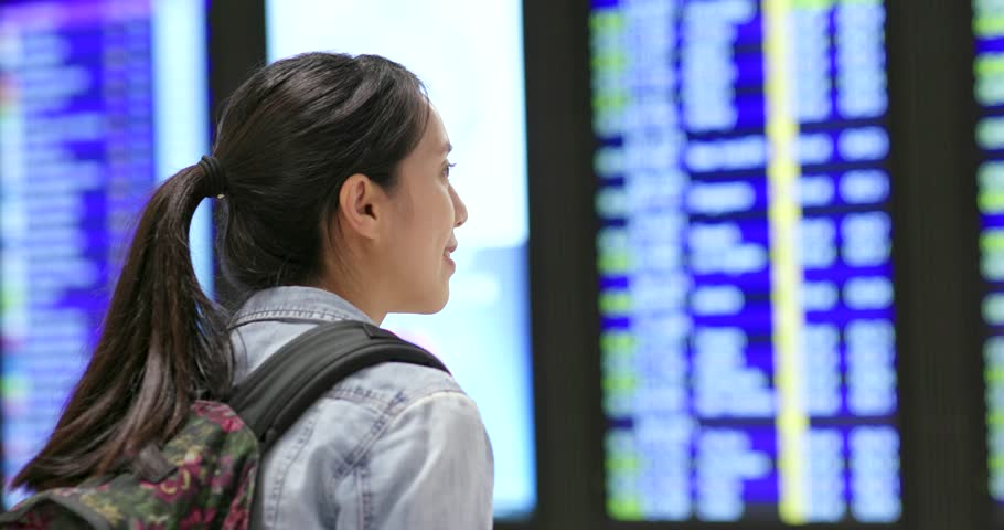 Travel woman looking at the display board in the airport | Shutterstock HD Video #1013075786