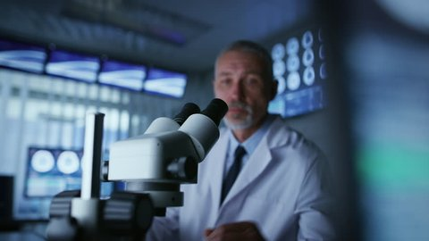 Senior Medical Research Scientist Looking under the Microscope in the Laboratory. Neurologist Solving Puzzles of the Mind and Brain. Shot on RED EPIC-W 8K Helium Cinema Camera.