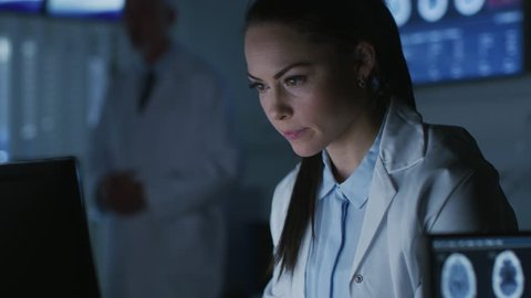Female Medical Research Scientist / Neurologist Working on a Personal Computer in Modern Laboratory. Making New Discoveries in the fields of Neurophysiology. Shot on RED EPIC-W 8K Helium Camera.