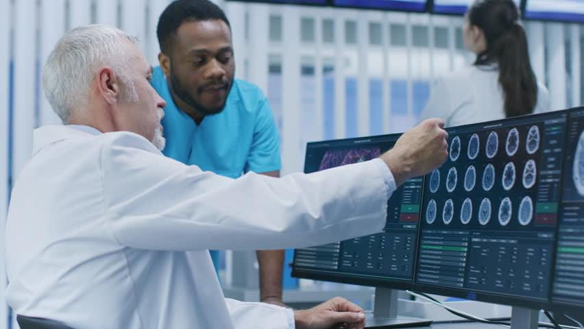 Medical Scientist and Surgeon Discussing CT / MRI Brain Scan Images on a Personal Computer in Laboratory. Neurologists / Neuroscientists in Neurological Research Center. Shot on RED EPIC-W 8K Helium C