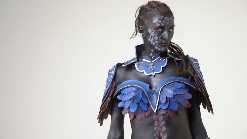 Woman cosplay anime character in black body art, posing in studio