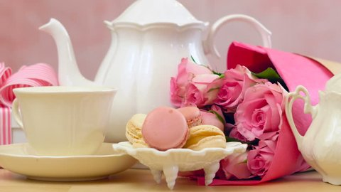 Mother's Day tea setting with teapot, macaron cookies, pink roses and gift.