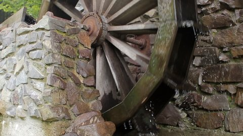 Old wooden water wheel turning under power