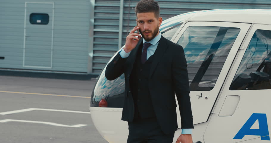 Young adult businessman executive talking on the phone near a private charter helicopter on a helipad. 4K UHD