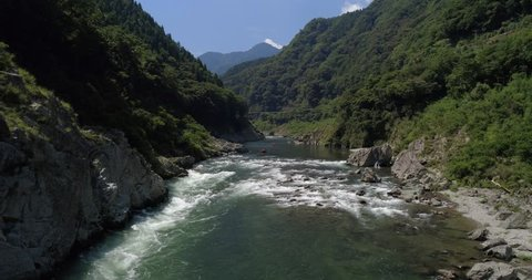 Aerial slow approach shot of people rafting on the Yoshino River in Tokushima Japan