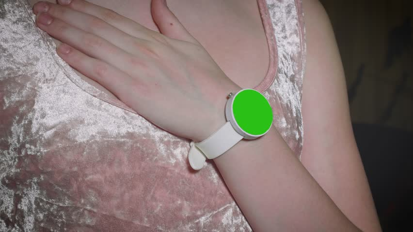 Part of girl's party. Girl puts hand with green screen watches on breast