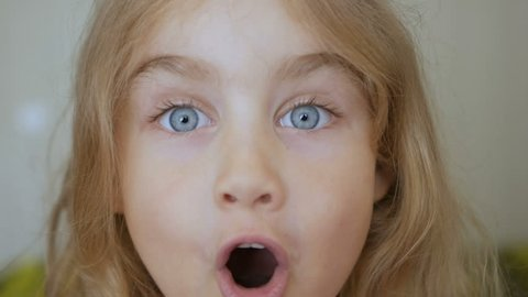 Girl looks and is surprised and happy to receive a surprise. Portrait little young girl with blue eyes looking at camera. Closeup