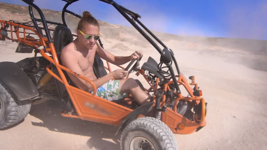 Driver man ride on sand buggy car in desert. Close up of extreme man riding on desert car around. Summer extreme. Desert racing car. Hipster man enjoy safari travel. Extreme holiday