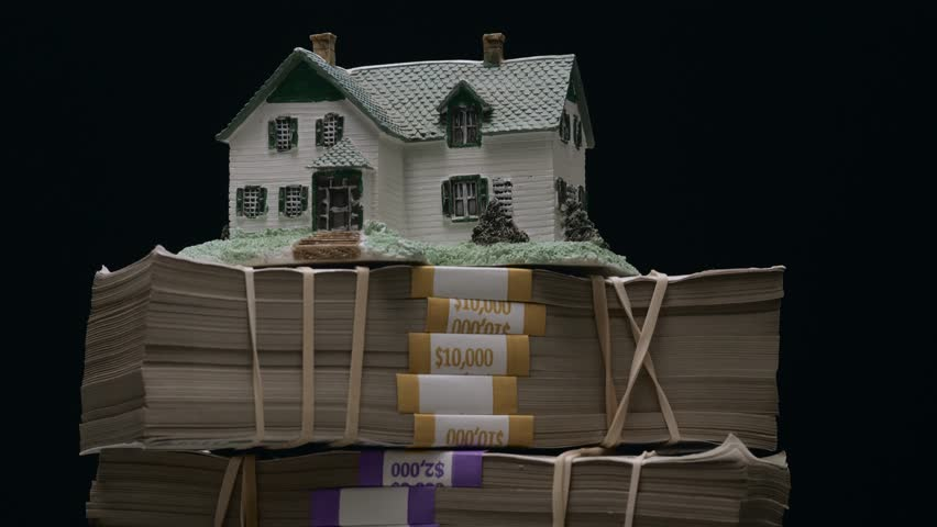 House on top of a large stack of money bills. Real estate mortgage concept shot. | Shutterstock HD Video #1013155346