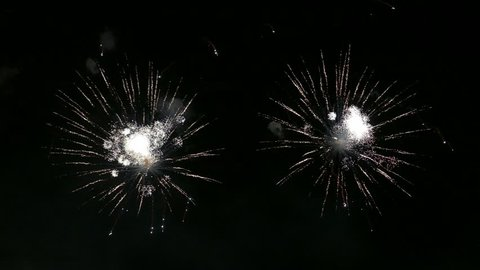 Ungraded: Flashes of fireworks festively sparkling in night sky against background of smoke blown away by wind.