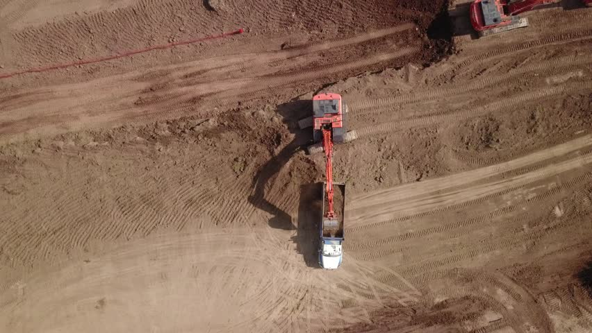 Aerial drone footage (top view) of a construction site.  Heavy equipment is grading the land, moving and flattening out red clay soil.