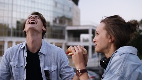 Happy, young couple are hanging out in the park. Lauging and smiling. Girl is eating burger. The young guy gently wipes the sauce off his girl's lips and licks a finger. Close up