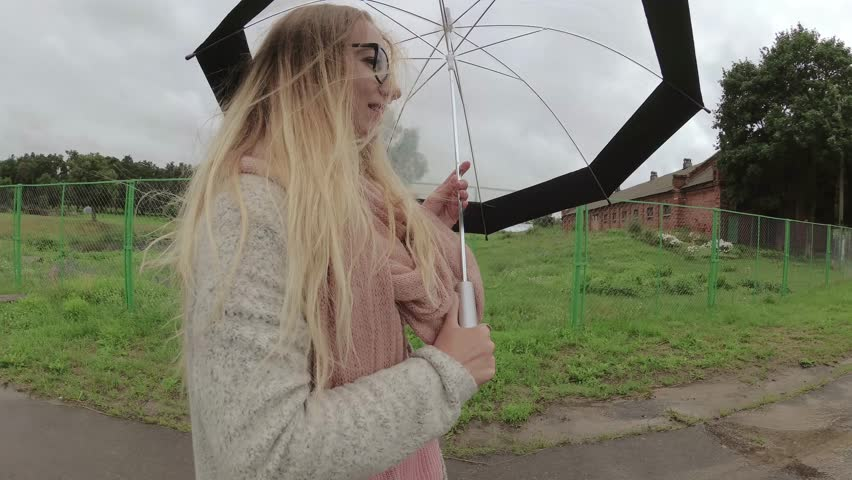 Girl under an umbrella in bad weather. | Shutterstock HD Video #1013185166
