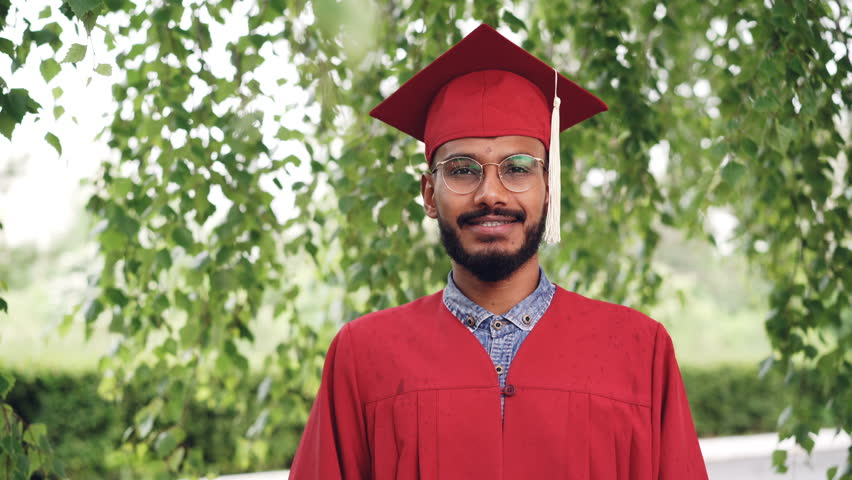 Portrait of bearded mixed race man graduating student in gown and mortar-board smiling and looking at camera standing outdoors on campus. People and education concept.
