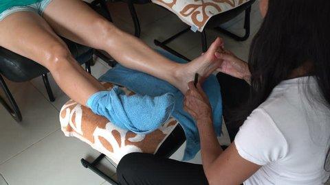 The masseuse uses a teak wand for foot reflexology