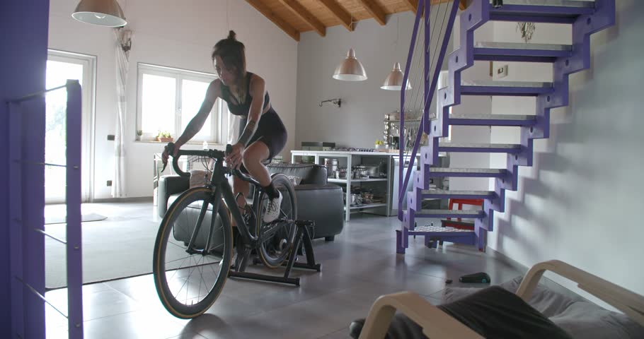 Young tattooed cyclist woman cycling with bicycle at home fitness sport workout .Living room domestic training. 4k slow motion video