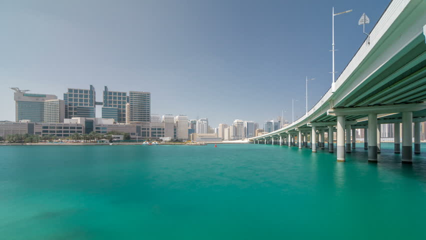 Modern buildings in Abu Dhabi skyline timelapse hyperlapse with mall and beach. View from the waterfront of Al Maryah Island with reflections in water near bridge