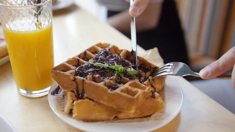 Male hands cuts a yummy belgian waffles with a knife and fork in restaurant