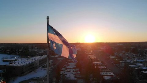 Slow motion drone view of the Quebec flag, with the sunset in the background