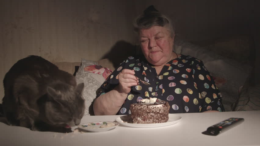 Senior woman with cat watching television in a dark room. Elderly woman with her cat at the table eating together in front of TV at night.