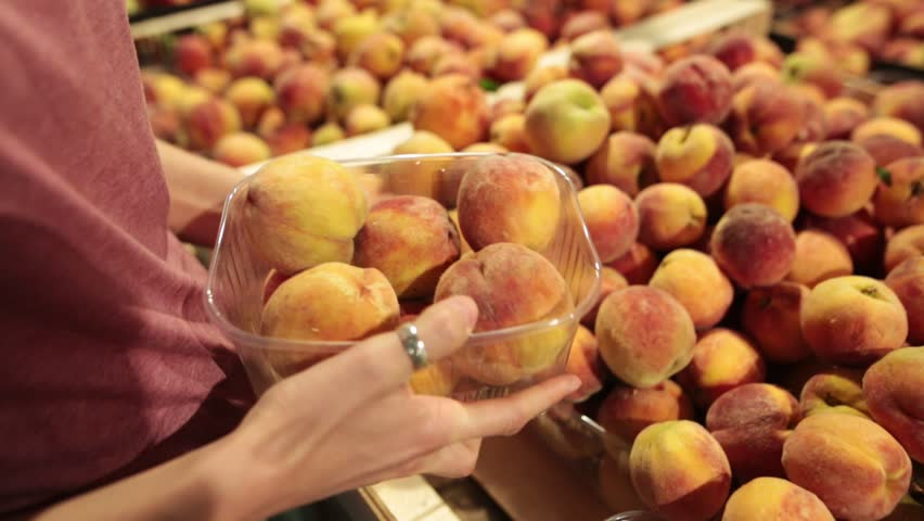 A woman chooses peaches on the store counter. A woman's hand puts the peaches in a bag. Closeup shot.