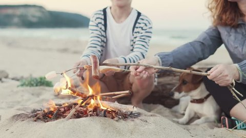 The son and his mother roast marshmallow, sausages and bread on sticks. Family camping on the beach in the evening at sunset. Campers rest on summer vacations at the sea and prepare their. A family