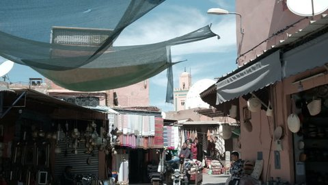 Marrakech, morocco - march 26, 2018: camera tracking right view outside  traditional souq marketplace with view of ben youssef madrasa minaret