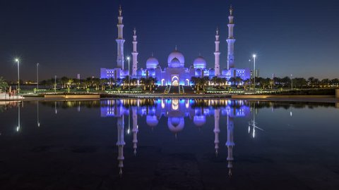 Sheikh Zayed Grand Mosque illuminated at night timelapse, Abu Dhabi, UAE. Evening view from Wahat Al Karama with reflections on water. The 3rd largest mosque in the world