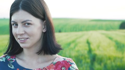 beautiful European girl with short black hair in short skirt with flowers looks at the camera, starts to laugh and turns away by hiding his hand against the background of the green rye field