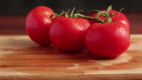 fresh tomatoes with water drops on wooden board