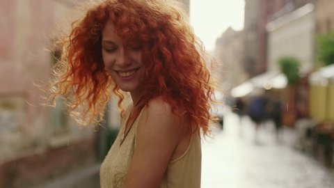 Cute woman with red curly hair walking in the rain on the street look at camera spinning happy smile beautiful portrait fashion water silhouette summer face female lonely stop close up