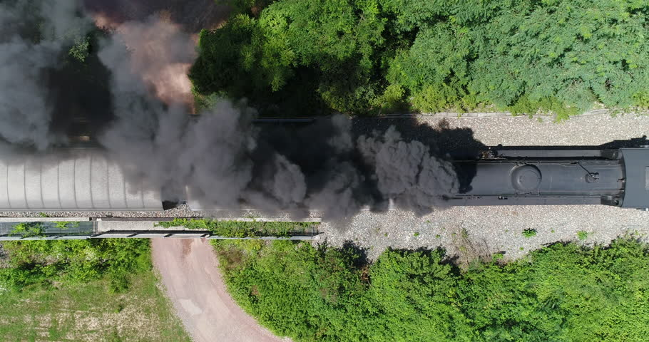 Aerial view of steam train running on the tracks in the countryside. Heritage historic steam locomotive with black smoke seen from above by drone.