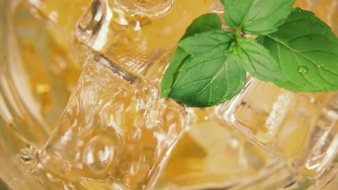 Slow motion yellow drink beautifully pour into a glass with ice and mint leaves top view close-up